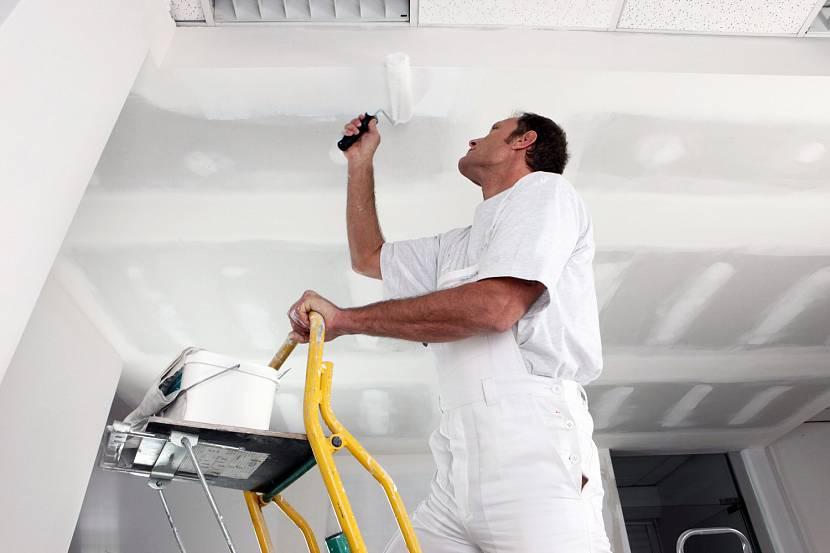 Мастер окрашивает потолок по оштукатуренному гипсокартону