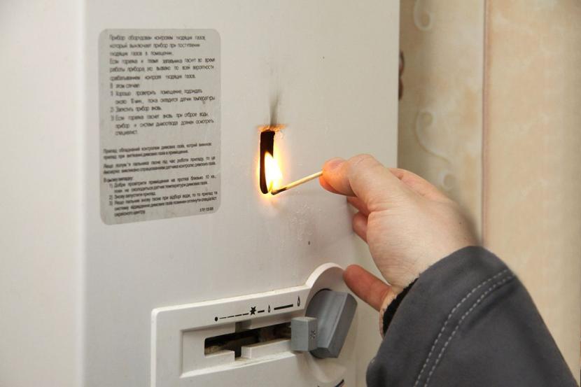 Проверка тяги в газовой колонке зажжённой спичкой
