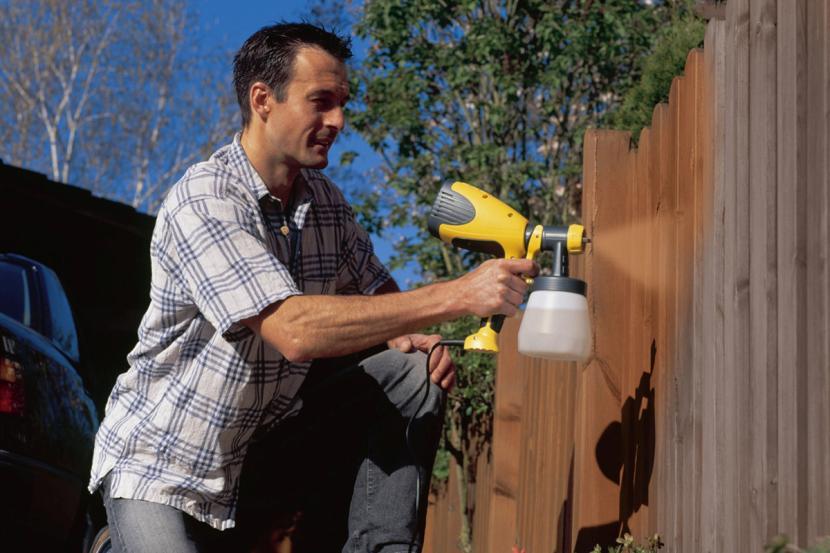 Нанесение краски на забор для защиты от пожара