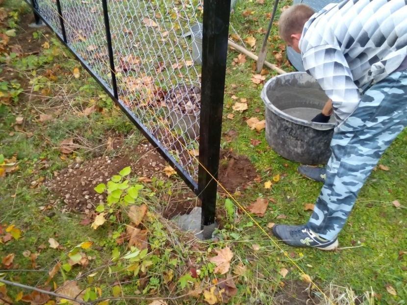 Заливка бетона для установки забора из сетки рабицы